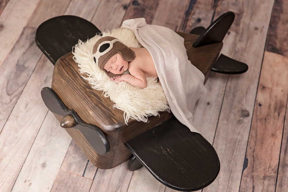 newborn photo prop - baby lay down on wood airplane